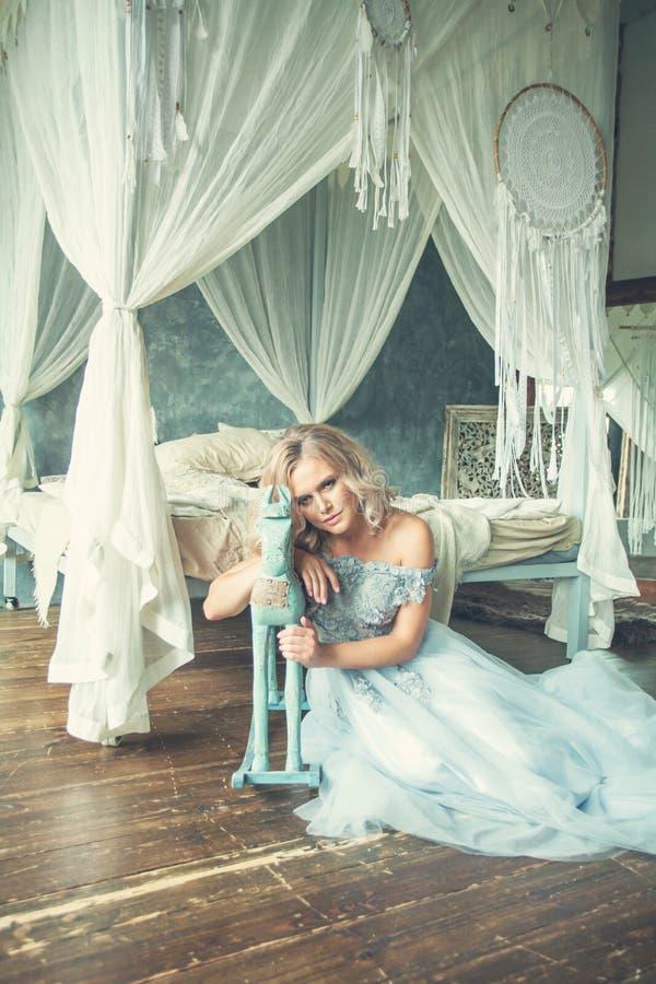 Mulher loura sensual em claro - vestido azul do tule no retrato interior do vintage luxuoso imagens de stock royalty free