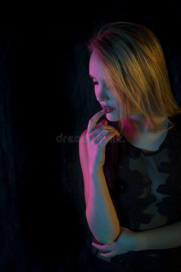 Mulher loura sensual no levantamento superior do laço preto na iluminação colorida na frente do fundo preto imagens de stock