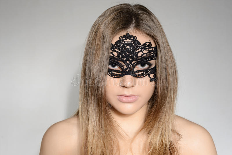 Mulher loura sensual nova do retrato na máscara do laço fotografia de stock royalty free