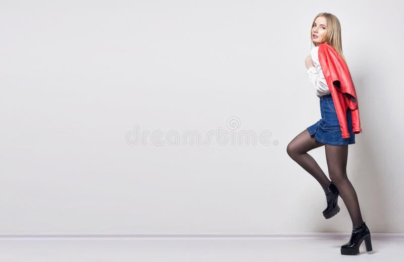 Mulher loura 'sexy' bonita do modelo na camisa e na saia Menina com o corpo perfeito que levanta estar Cabelo bonito e pés longos imagens de stock