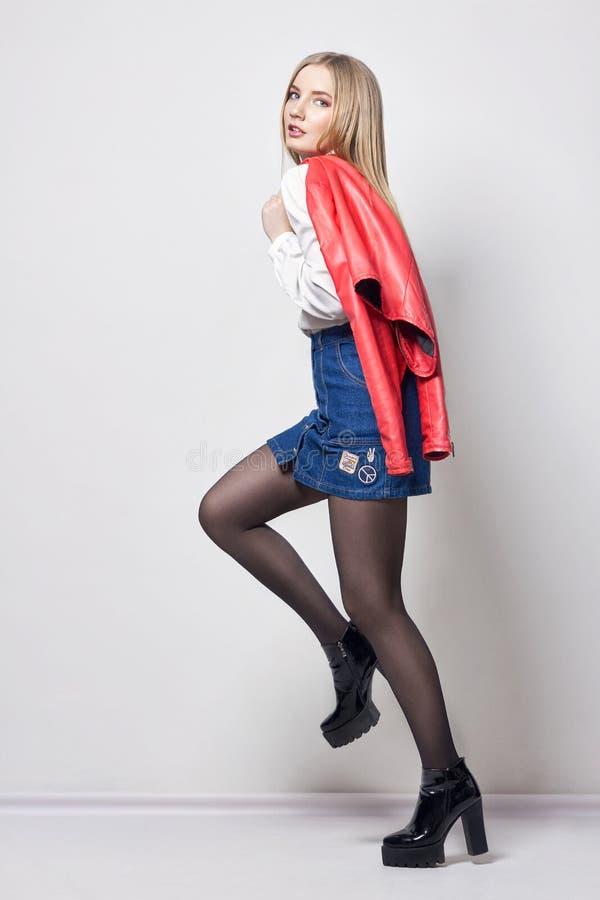 Mulher loura 'sexy' bonita na camisa e na saia Menina com o corpo perfeito que levanta estar O cabelo bonito e os pés longos, lis imagens de stock
