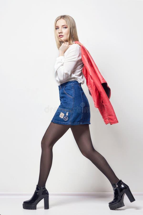Mulher loura 'sexy' bonita na camisa e na saia Menina com o corpo perfeito que levanta estar O cabelo bonito e os pés longos, lis imagens de stock royalty free