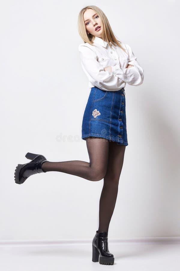 Mulher loura 'sexy' bonita na camisa e na saia Menina com o corpo perfeito que levanta estar O cabelo bonito e os pés longos, lis fotografia de stock royalty free