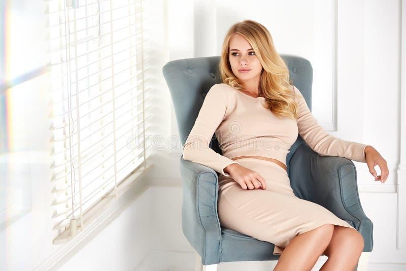 A mulher loura 'sexy' bonita senta a pele perfeita do cosmético da cara da cadeira fotos de stock royalty free