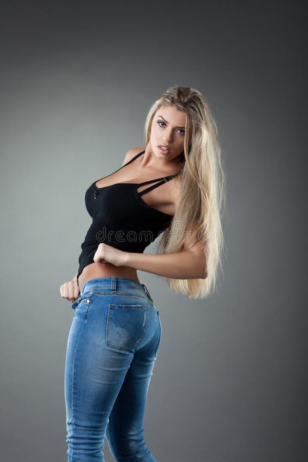 Mulher loura 'sexy' nas calças de brim fotografia de stock royalty free