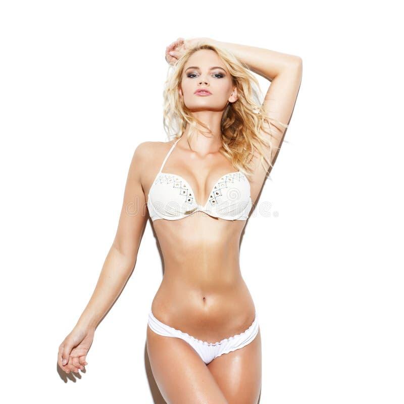 Mulher loura 'sexy' no biquini que levanta na parede branca fotos de stock royalty free