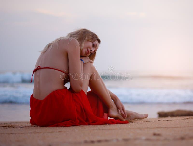 Mulher loura 'sexy' no biquini vermelho que senta-se na areia da praia no recurso tropical imagens de stock