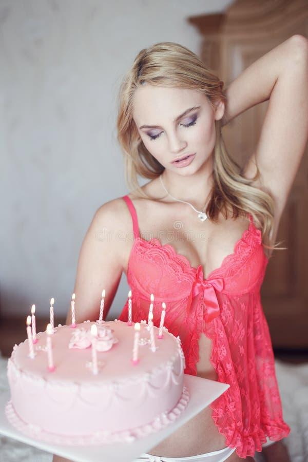 Mulher loura 'sexy' no sutiã cor-de-rosa com bolo de aniversário fotos de stock