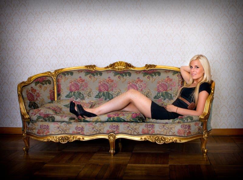 Mulher loura 'sexy' que deita no sofá fotografia de stock