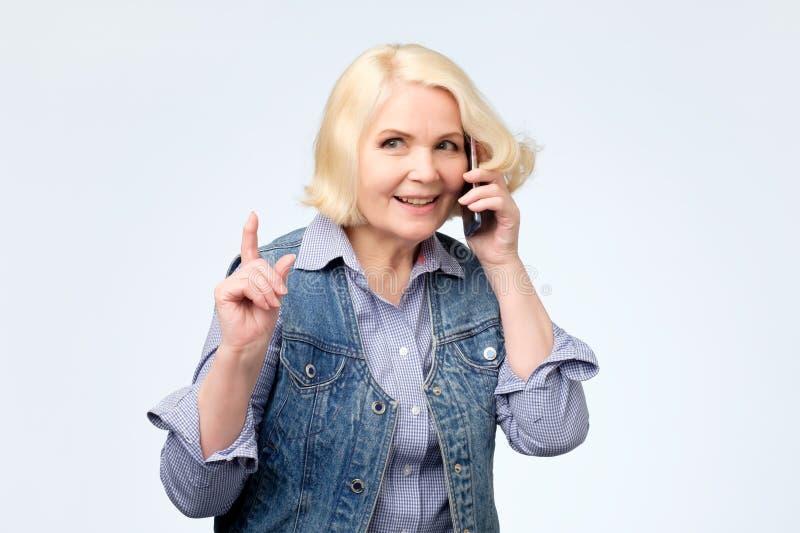 Mulher loura superior de sorriso que fala no telefone fotos de stock