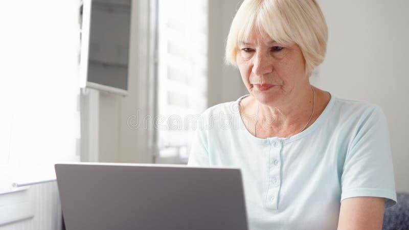 Mulher loura superior idosa que trabalha no laptop em casa Trabalho autônomo remoto na aposentadoria imagens de stock