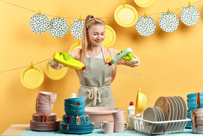Mulher loura trabalhadora que mistura detergentes diferentes da lavagem da louça imagem de stock royalty free