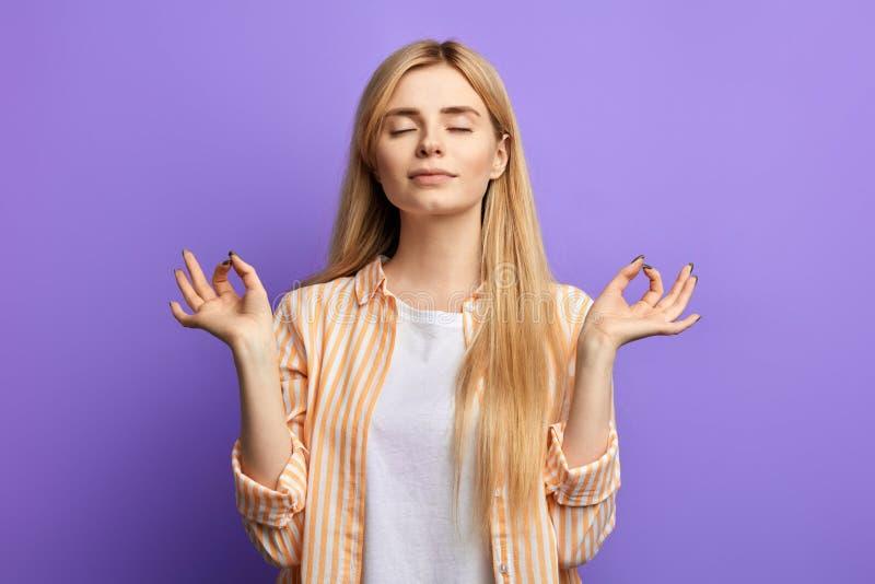 Mulher loura vestida em camisa listrada e no t-shirt branco que fazem a ioga fotos de stock