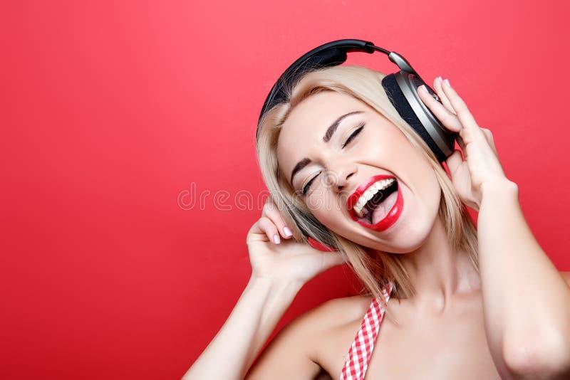 Mulher louro-de cabelo nova com fones de ouvido fotos de stock royalty free