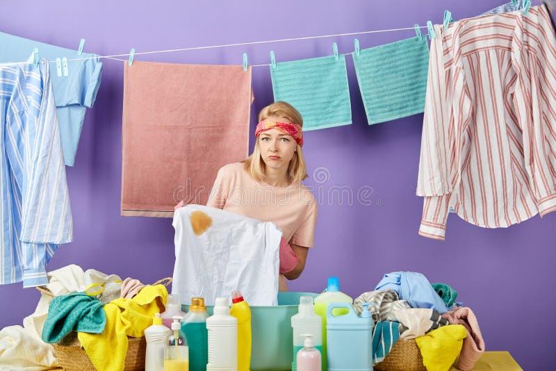 Mulher louro infeliz triste que guarda o t-shirt sujo foto de stock