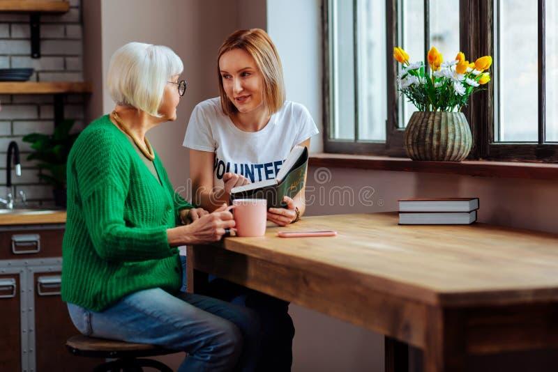 Mulher louro nova de encantamento que discute com o livro de cabelos curtos da Bíblia do pensionista fotografia de stock royalty free