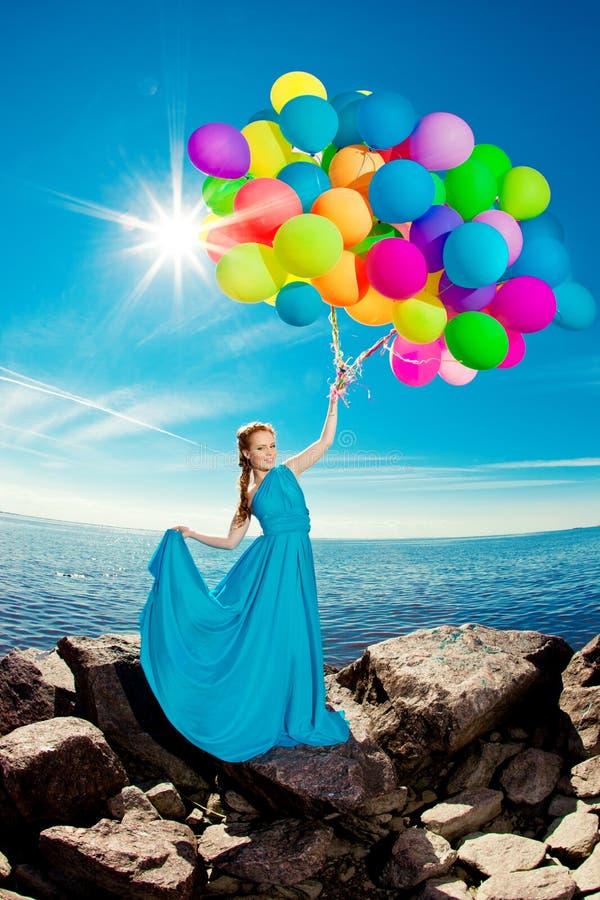 Mulher luxuosa da forma com balões à disposição na praia contra foto de stock royalty free