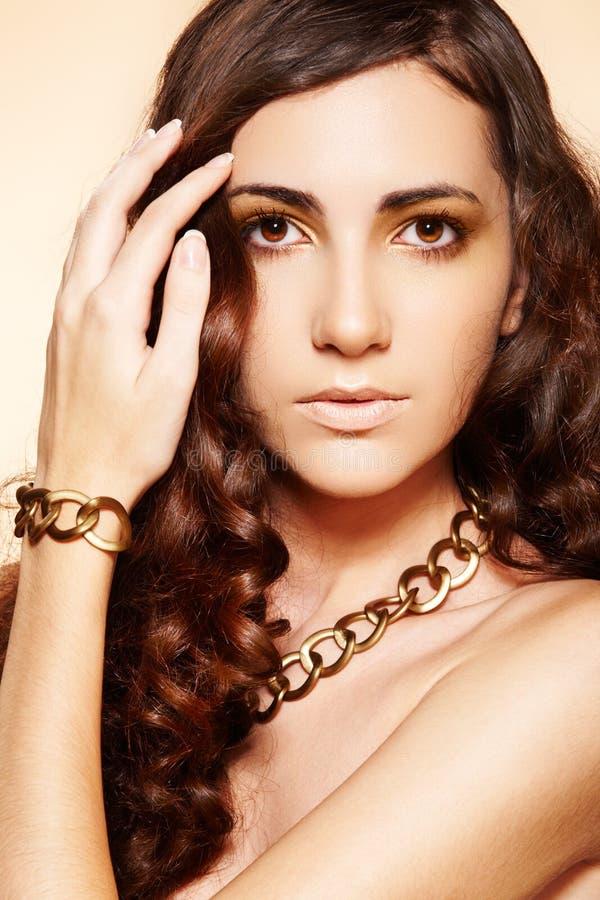 Mulher luxuosa da forma com os acessórios do ouro do encanto imagem de stock