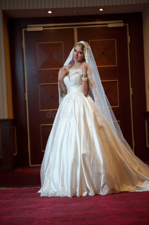 Mulher luxuoso bonita nova no vestido de casamento que levanta no interior luxuoso Noiva elegante lindo com véu longo Comprimento fotos de stock royalty free