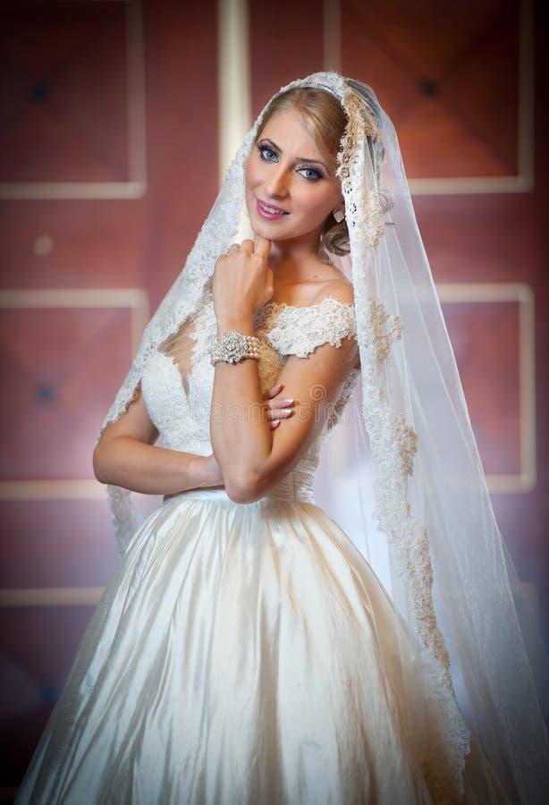 Mulher luxuoso bonita nova no vestido de casamento que levanta no interior luxuoso Noiva elegante lindo com véu longo Comprimento imagens de stock