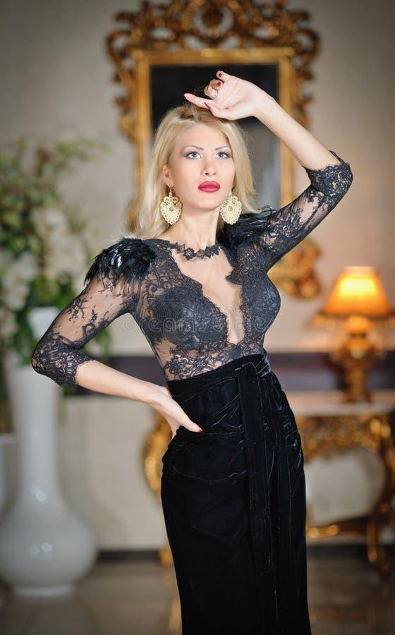 Mulher luxuoso bonita nova no vestido preto elegante longo. Mulher loura nova bonita com um espelho no fundo fotos de stock royalty free
