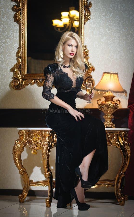 Mulher luxuoso bonita nova no vestido preto elegante longo. Mulher loura nova bonita com um espelho no fundo fotografia de stock