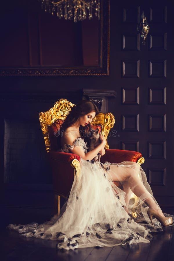 Mulher luxuoso bonita que senta-se com sphynx do gato fotografia de stock