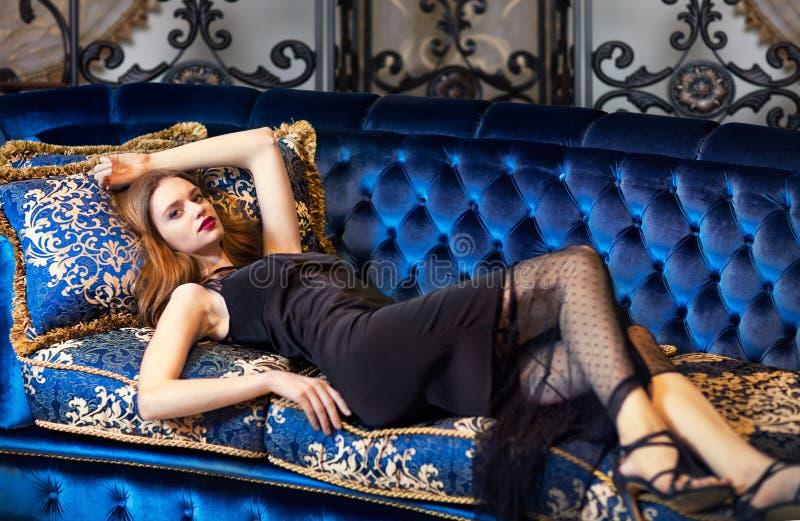 Mulher luxuoso que encontra-se em um sofá do vintage foto de stock royalty free