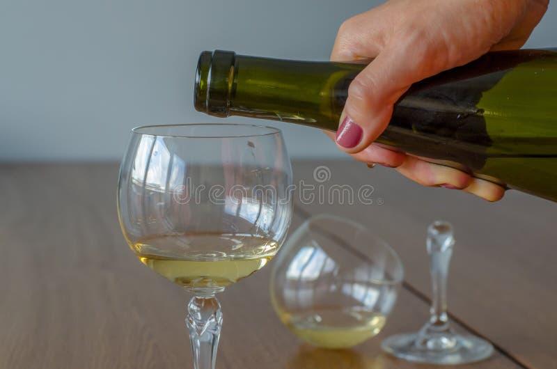 A mulher a mão do ` s que derrama o vinho branco em um vidro contra borrado quebrou fotografia de stock