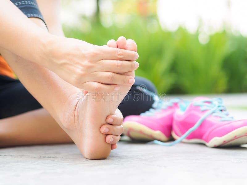 Mulher macia do foco que faz massagens seu pé doloroso ao exercitar imagens de stock