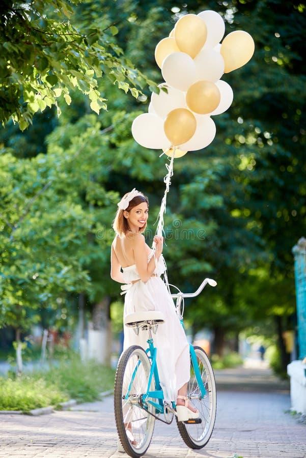 A mulher macia na bicicleta do vintage com balões olha com sorriso fotos de stock royalty free
