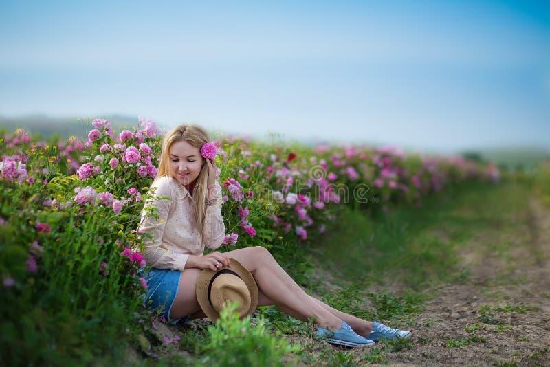 Mulher macia nova bonita que anda no campo das rosas de chá As calças de brim vestindo da senhora loura e o chapéu retro apreciam fotos de stock royalty free