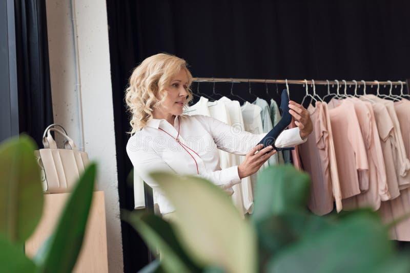 mulher madura à moda que escolhe sapatas imagem de stock royalty free