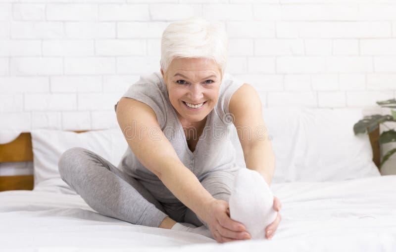 Mulher madura alegre de encantamento que estica seus pés imagens de stock royalty free