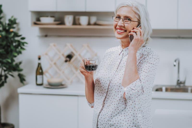 A mulher madura alegre está tendo o café ao falar no telefone imagens de stock