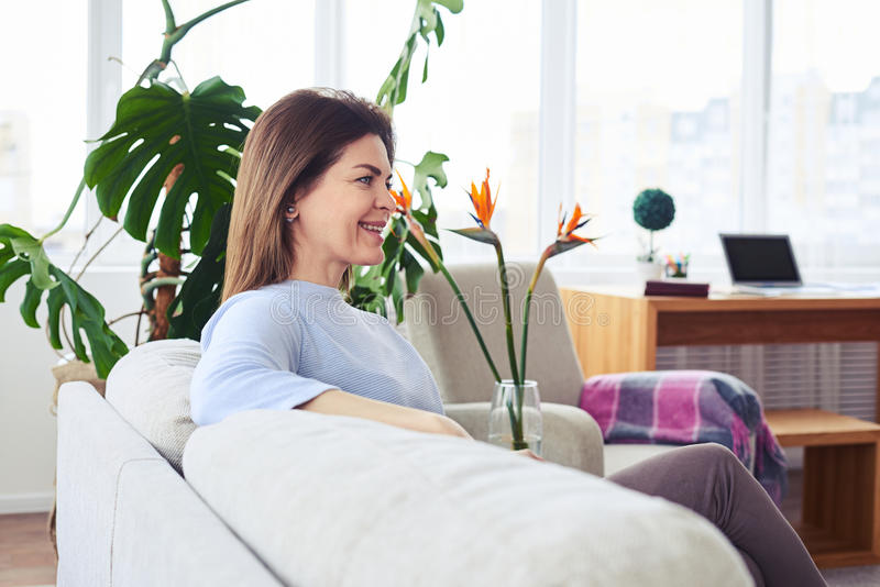 Mulher madura atraente que senta-se no sofá na sala de visitas brilhante fotos de stock