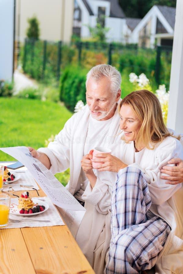 Mulher madura atraente que veste a calças esquadrada do pijama que senta-se perto do marido imagem de stock royalty free