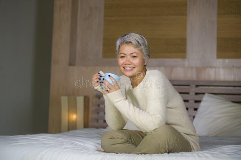 A mulher madura atrativa e bem sucedida com o cabelo cinzento que senta-se no caf? bebendo da cama relaxou o sorriso feliz como a imagem de stock royalty free