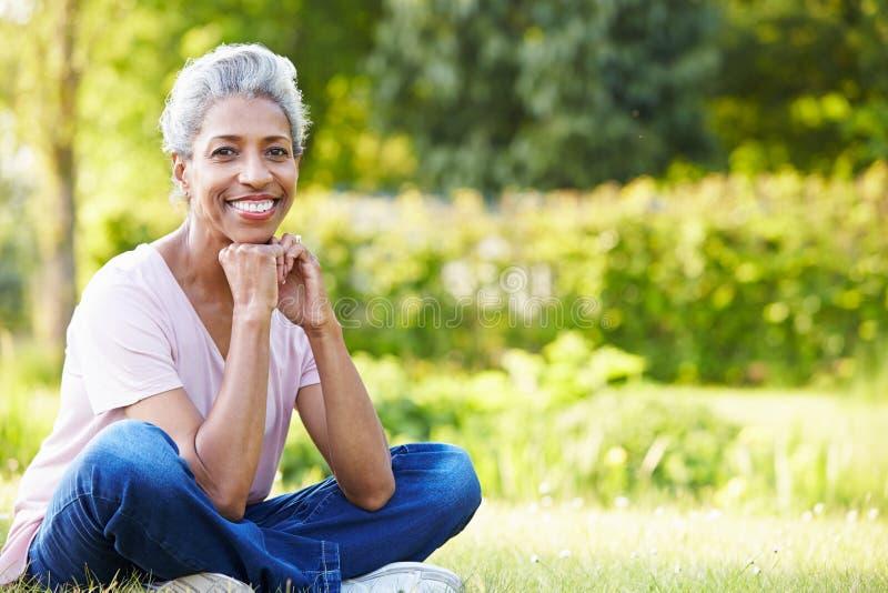 Mulher madura atrativa que senta-se no jardim fotografia de stock royalty free