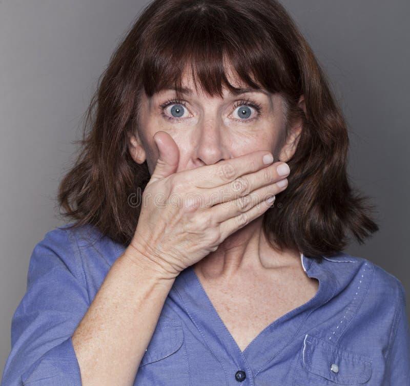 Mulher madura atrativa surpreendida que esconde sua boca imagem de stock