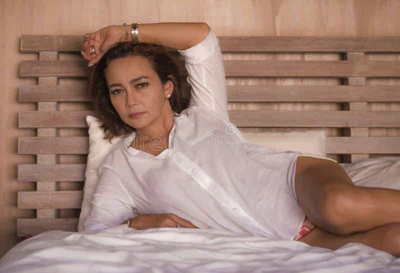 A mulher madura bem sucedida e 'sexy' atrativa envelheceu 50s a 60s relaxado e em casa ao quarto seguro que encontra-se na cama n fotografia de stock royalty free