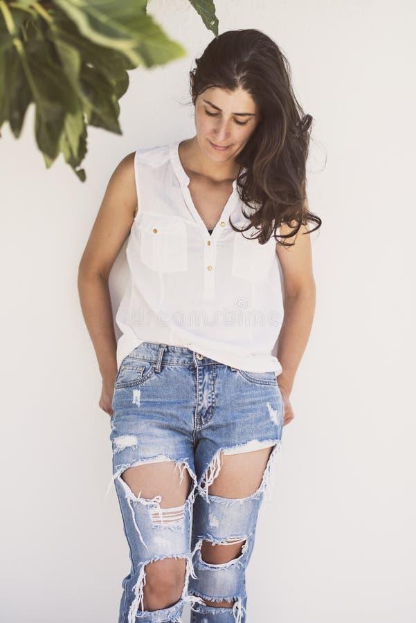 Mulher madura bonita com estilo moderno com calças de brim quebradas fotos de stock