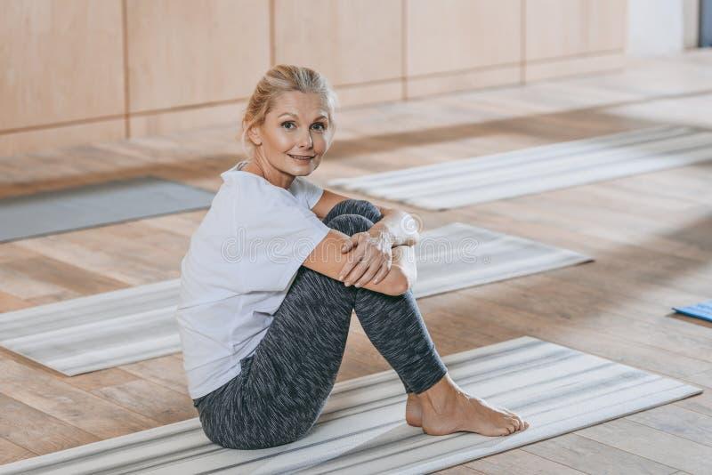 mulher madura bonita que senta-se na esteira da ioga e que sorri na câmera imagens de stock