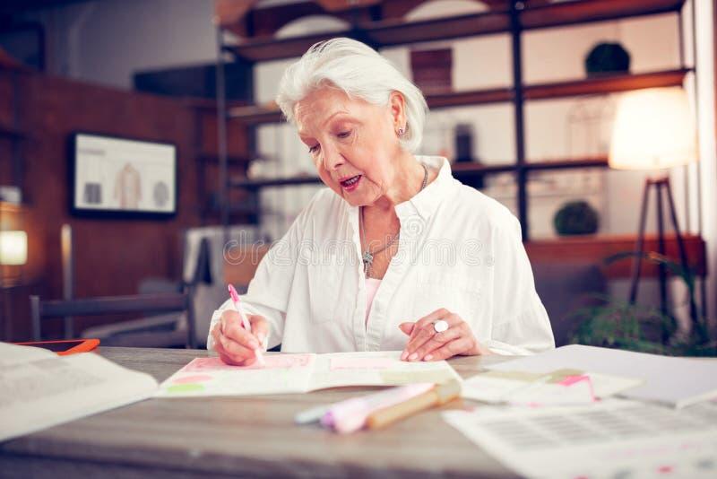 mulher madura Cinzento-de cabelo com a composição agradável que faz algumas anotações fotografia de stock royalty free