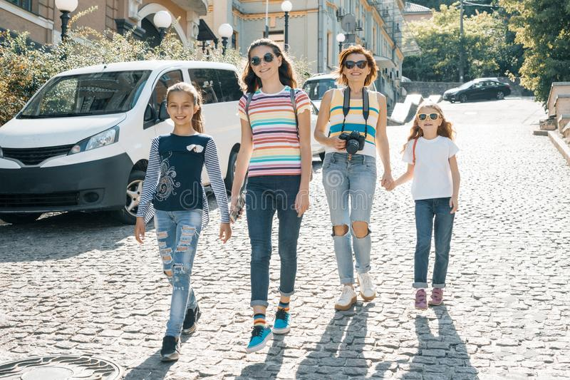 Mulher madura com as crianças que andam em uma rua da cidade no dia ensolarado do verão imagem de stock royalty free