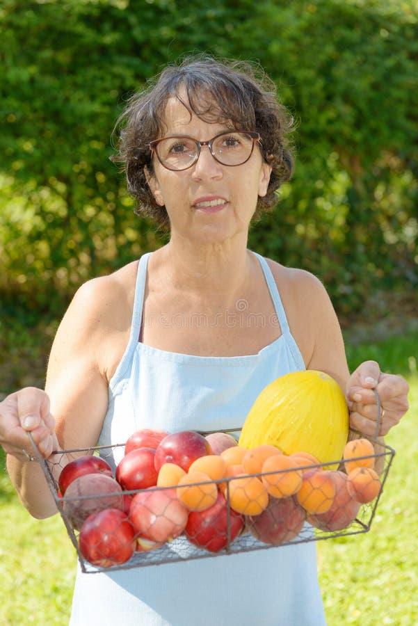 Mulher madura com cesta de fruto imagem de stock royalty free