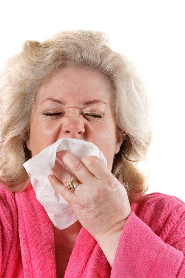 Mulher madura com gripe que sneezing foto de stock