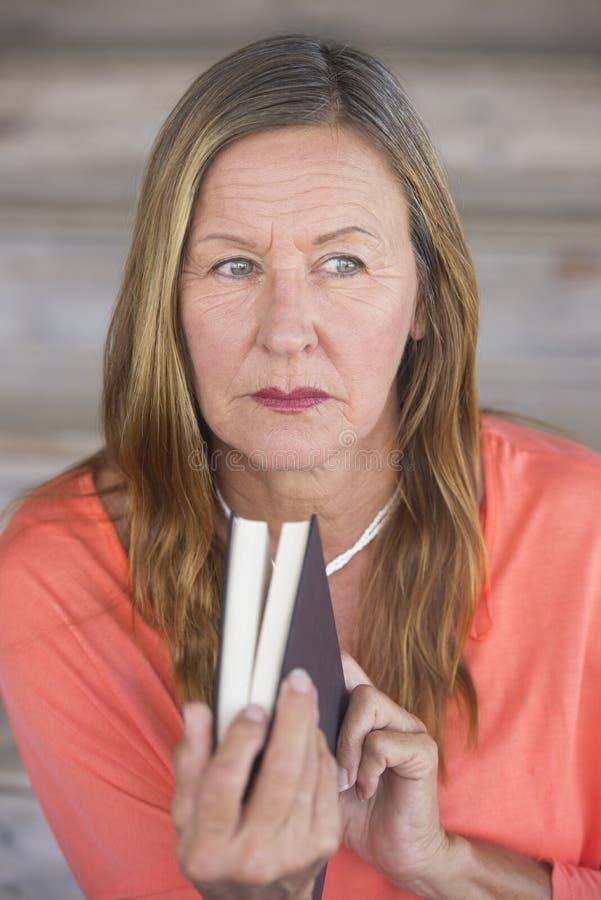 Mulher madura com o concernd do livro pensativo fotos de stock royalty free