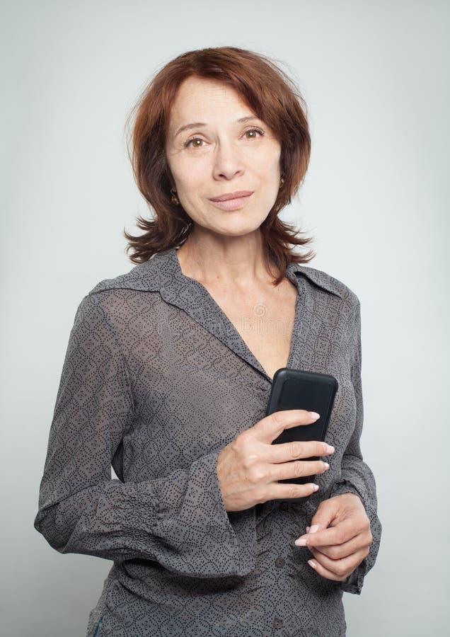 Mulher madura com o smartphone no branco foto de stock