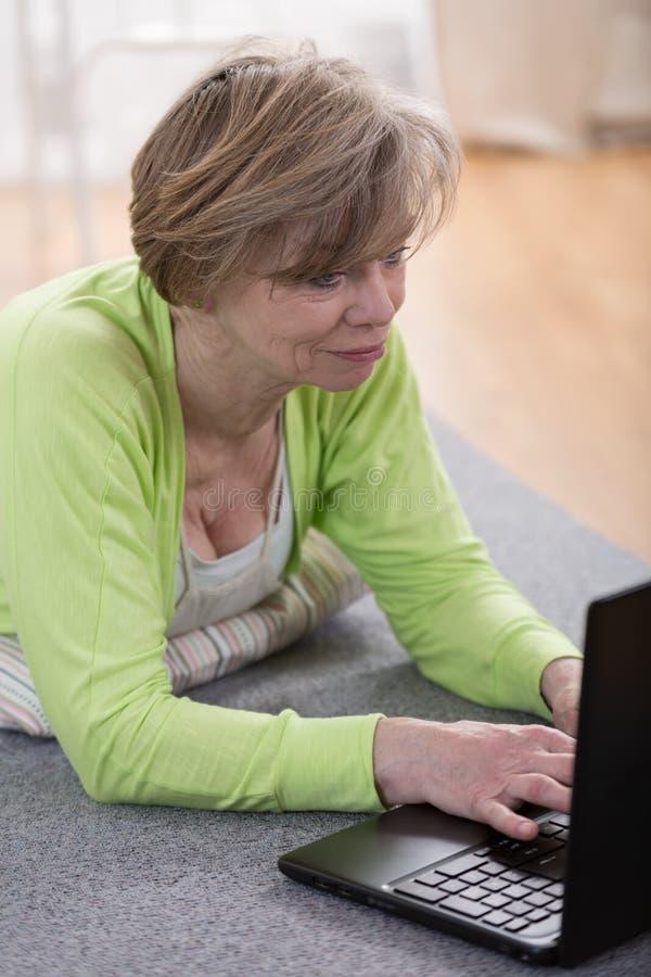 Mulher madura com portátil imagens de stock royalty free